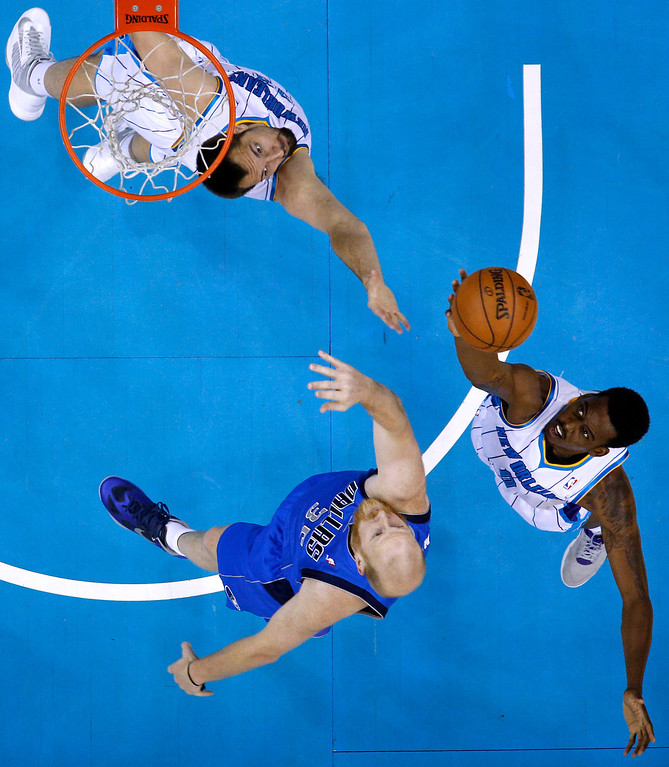 . New Orleans Hornets power forward Ryan Anderson, top, Dallas Mavericks center Chris Kaman, center, and New Orleans Hornets small forward Al-Farouq Aminu, right compete for a rebound during the first half of an NBA basketball game in New Orleans, Sunday, April 14, 2013. The Mavericks won 107-89. (AP Photo/Jonathan Bachman)