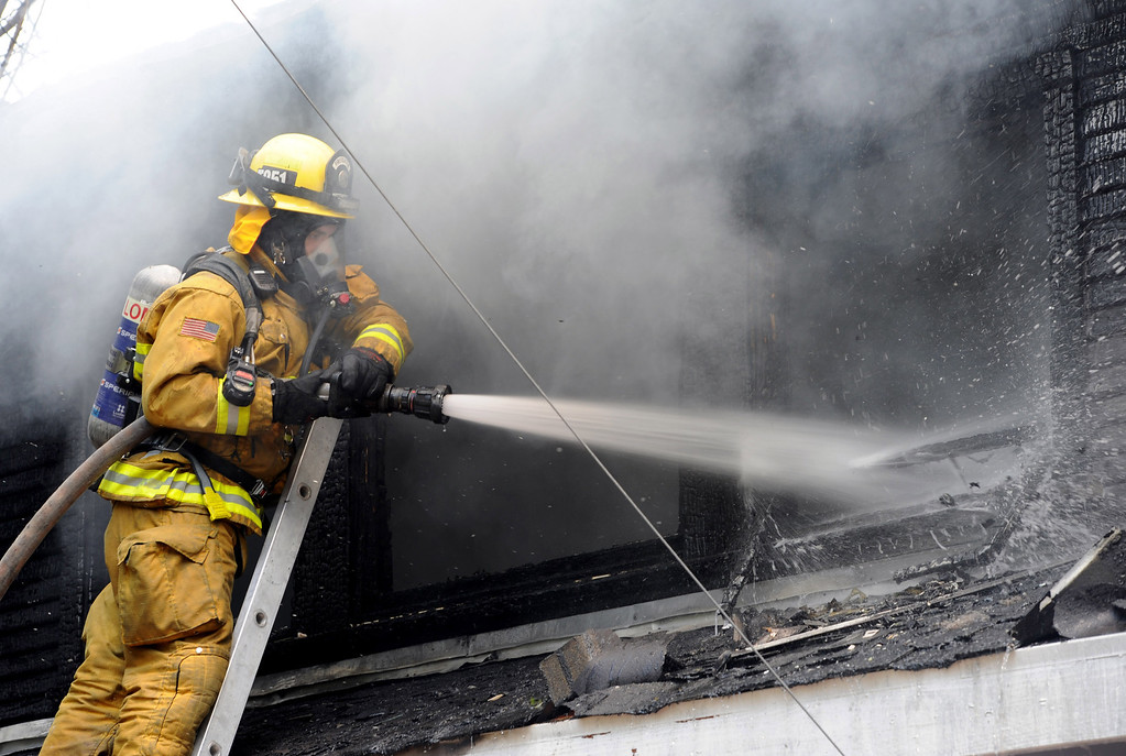 . A Loma Linda fire fighter works a house fire that started at 11:33 am, along Olive Ave. in Redlands,Ca., Wednesday, April 8, 2014. Firefighters from Redlands, San Bernardino County and San Bernardino Fire Departments, Loma Linda, as well as Cal Fire battled a two-alarm fire that destroyed a historic home in Redlands. (Photos by John Valenzuela/Redlands Daily Facts)