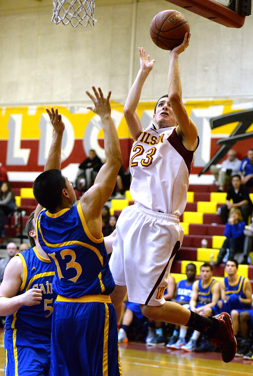 . Wilson\'s Erick Ramos (23) shoots over San Dimas\' Tony Hugo (13) in the first half of a prep basketball game at Wilson High School in Hacienda Heights, Calif., on Friday, Jan. 31, 2014. (Keith Birmingham Pasadena Star-News)