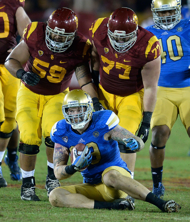 . UCLA #99 Cassius Marsh came up with the ball after is was stripped broom USC Cody Kessler in the 4th quarter. UCLA defeated USC 35 to 14 in a matchup of cross town rivals at the Los Angeles Memorial Coliseum in Los Angeles, CA.  photo by (John McCoy/Los Angeles Daily News)