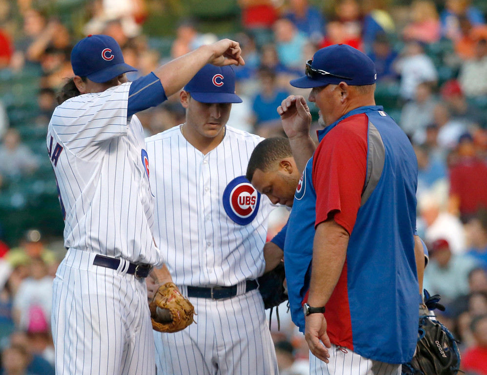 . Chicago Cubs starting pitcher Jeff Samardzija, left, wipes the sweat from his face as he listens to pitching coach Chris Bosio, right, with first baseman Anthony Rizzo and catcher Welington Castillo joining them at the mound during the first inning of an interleague baseball game against the Los Angeles Angels on Wednesday, July 10, 2013, in Chicago. (AP Photo/Charles Rex Arbogast)