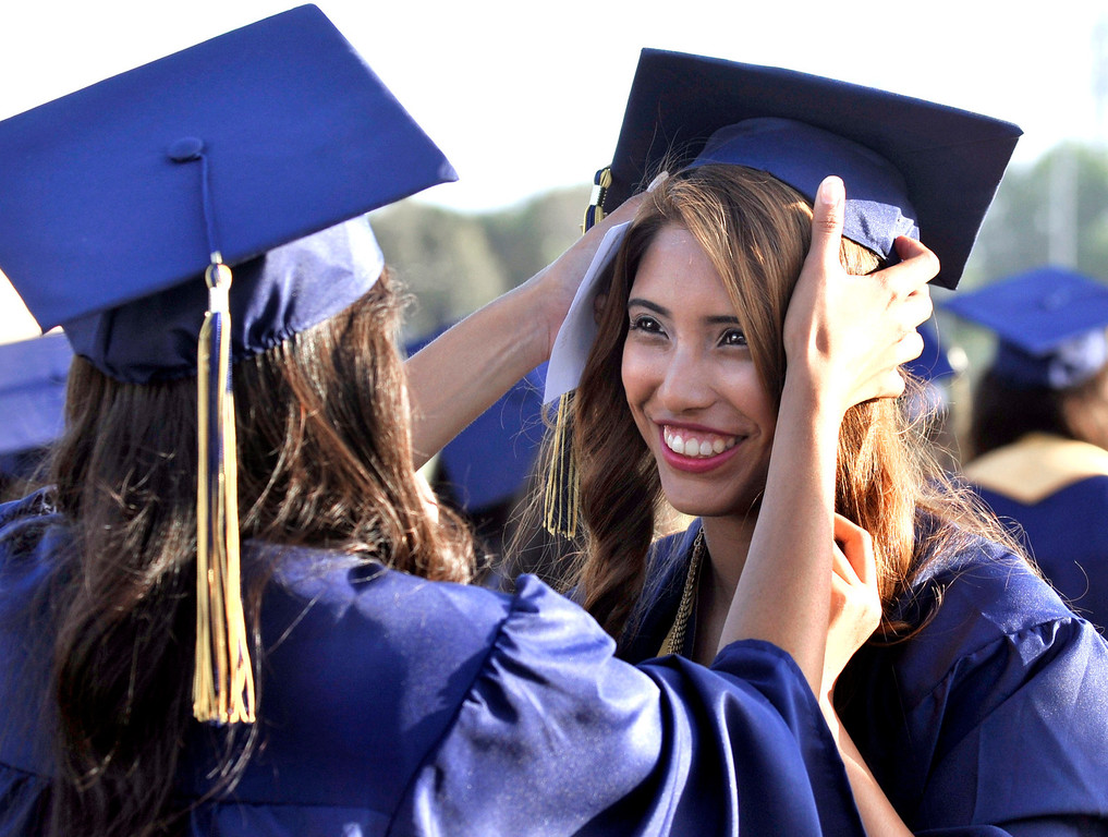 . Denise Martinez, right, get a little help from her friend Lizbeth (cq) DeLeon.  South El Monte High School Graduation on their football stadium, Wednesday, June 11,  2014.  (Mike Mullen photo)