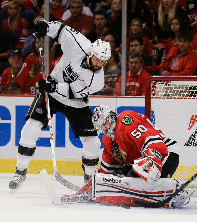 . Chicago Blackhawks goalie Corey Crawford (50) blocks a shot attempt by Los Angeles Kings left wing Dustin Penner (25) during the third period of Game 1 of the NHL hockey Stanley Cup Western Conference finals, Saturday, June 1, 2013, in Chicago. Chicago won 2-1. (AP Photo/Nam Y. Huh)