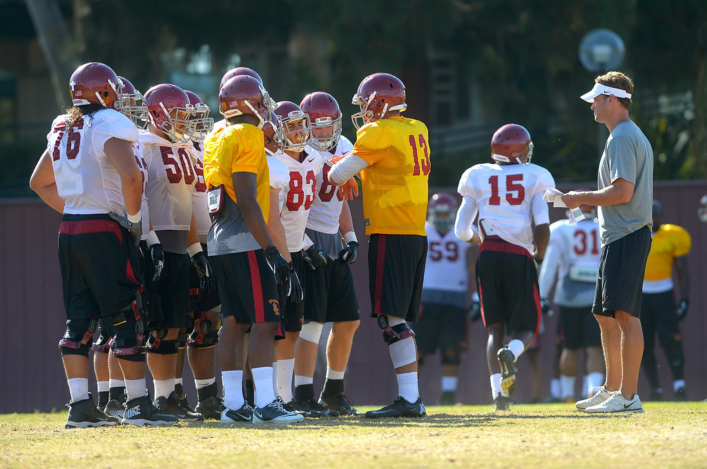 . Players gather around quarterback Max Wittek during a USC practice August 20, 2013.(Andy Holzman/Los Angeles Daily News)