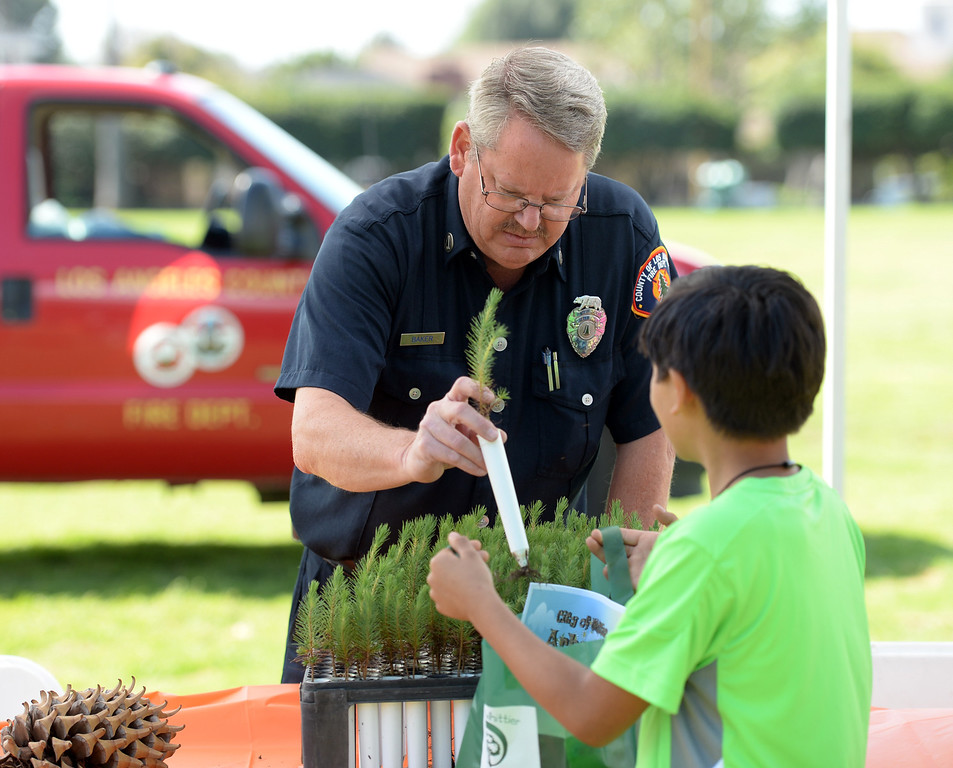 . Los Angeles County Deputy Forester, Jon Baker, gives out seedlings to school children during the Annual Arbor Day celebration at Michigan Park in Whittier on Thursday March 13, 2014. Children were able to help plant trees, see demonstrations by city workers and see information booths from area conservation groups. (Staff Photo by Keith Durflinger/Whittier Daily News)