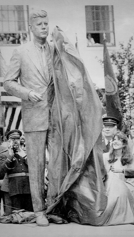 . Caroline Kennedy Schlossberg, right, daughter of President John F. Kennedy, pulls the shroud from the statue of her father in front of the Statehouse in Boston. (May 1990)   Los Angeles Daily News file photo