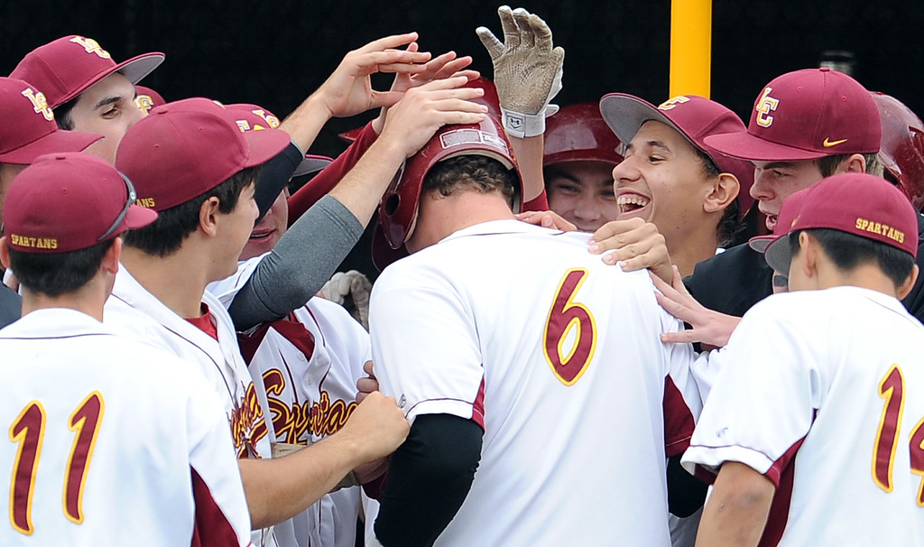 . La Canada\'s Anthony Mizrahi (6) is mobbed by his teammates after hitting a three run home run in the first inning of a prep baseball game against San Marino at La Canada High School on Wednesday, March 8, 2013 in La Canada, Calif. La Canada won 3-2.  (Keith Birmingham Pasadena Star-News)