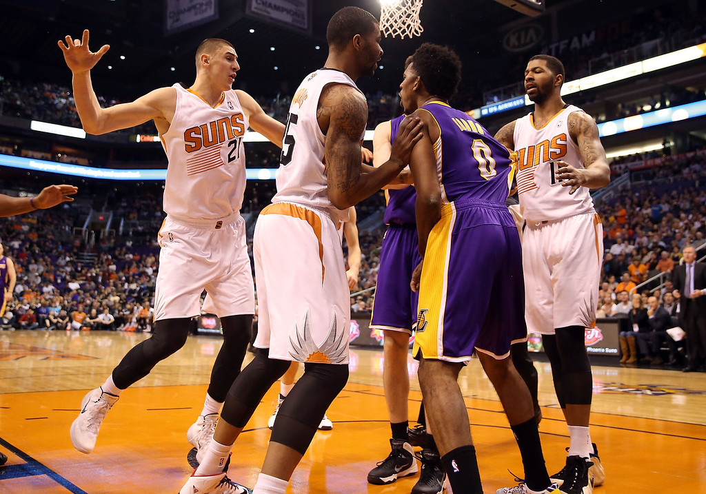 . Nick Young #0 of the Los Angeles Lakers reacts to Alex Len #21 of the Phoenix Suns after a flagrant foul as Marcus Morris #15 (L) and Markieff Morris #11 (R) hold him back during a scuffle in the first half of the NBA game at US Airways Center on January 15, 2014 in Phoenix, Arizona.    (Photo by Christian Petersen/Getty Images)