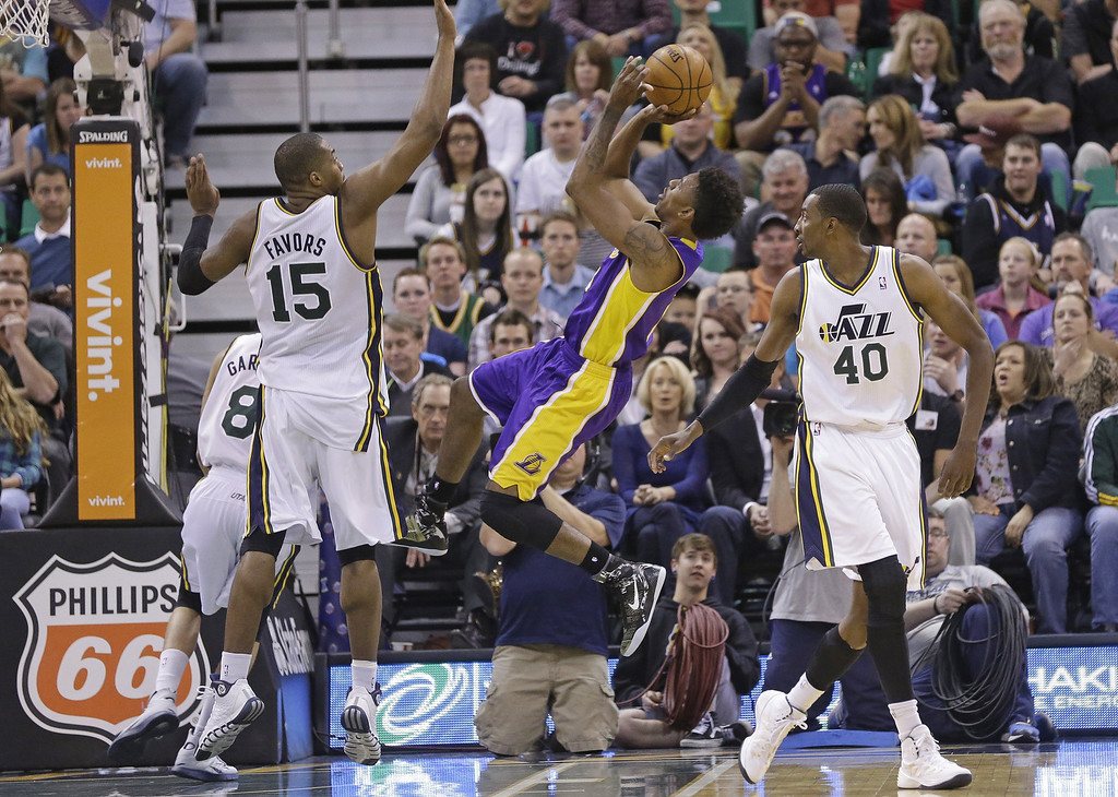 . Los Angeles Lakers Nick Young, center, shoots as Utah Jazz\'s Derrick Favors (15) defends and Jeremy Evans (40) looks on in the fourth quarter during an NBA basketball game Monday, April 14, 2014, in Salt Lake City, Utah. The Lakers won 119-104. (AP Photo/Rick Bowmer)