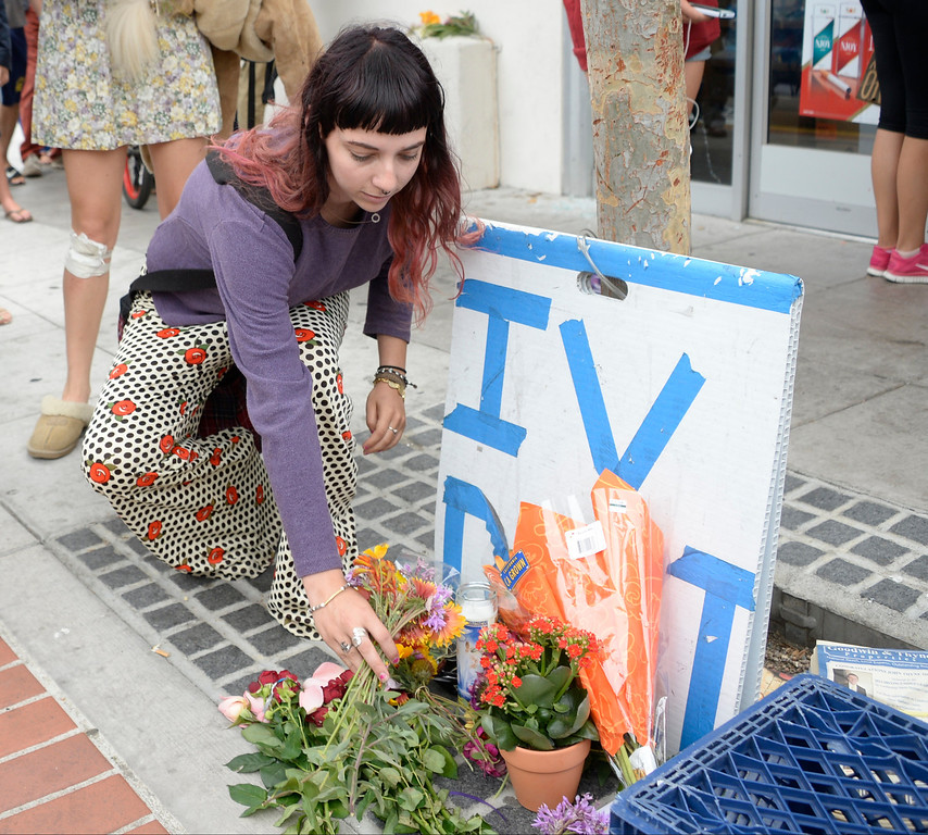 . May 24-,2014. Isla Vista, CA. UCSB student Megan Helsel lays down flowers at the sight where one person was killed by the drive-by shooting that left seven people dead Friday night, including the attacker, and seven others wounded, authorities said Saturday.  The gunman got into two gun battles with deputies Friday night in the beachside community of Isla Vista before crashing his black BMW into a parked car. Photo by Gene Blevins/LA Daily News