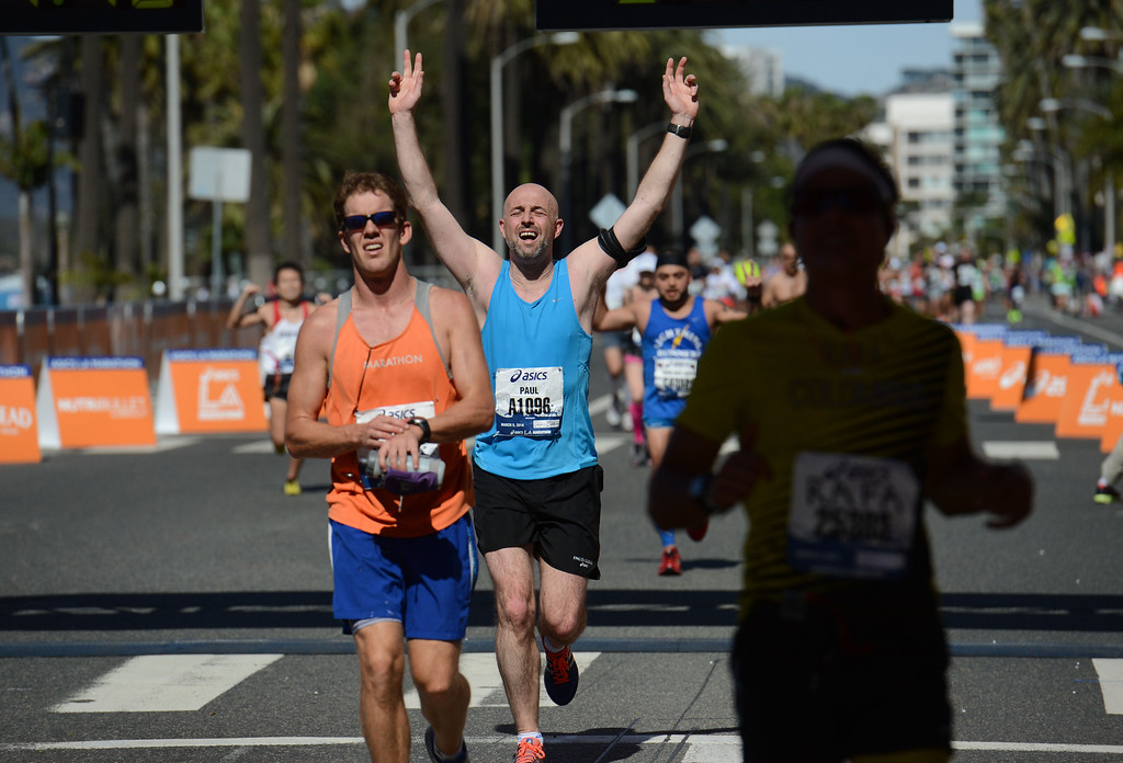 . Runners along Ocean Boulevard,  cross the finish line of  2014 ASICS LA Marathon finisher Bill Hopkins after feeling nauseous after he crossed the finish line in Santa Monica Calif,    Sunday, March 9,  2014. 