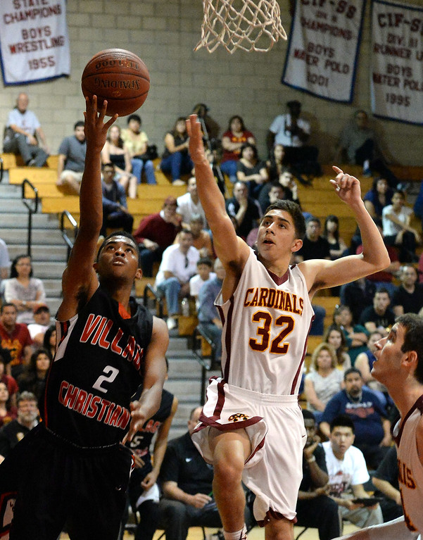 . Village Christian\'s Jerrick Ahanmisi (2) drives to the basket past Cantwell\'s Andrew Martinez (32) in the first half of a State Division 4 CIF Prep Playoff Basketball game at Whittier High School in Whittier, Calif., on Saturday, March 15, 2014. Cantwell won 51-48.  (Keith Birmingham Pasadena Star-News)