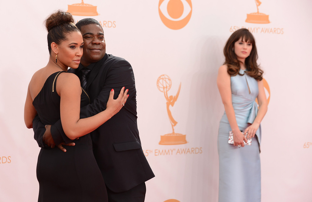. From left, Tracy Morgan, Megan Wollover and Zooey Deschanel arrive at the 65th Primetime Emmy Awards at Nokia Theatre on Sunday Sept. 22, 2013, in Los Angeles.  (Photo by Jordan Strauss/Invision/AP)