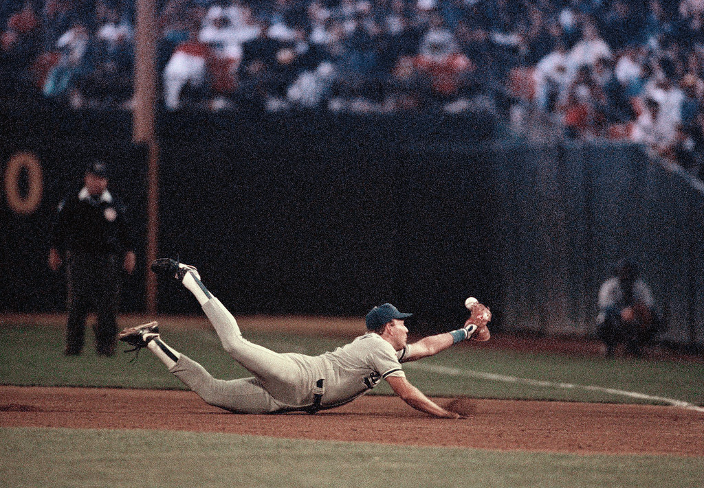 . Los Angeles Dodgers first baseman Tracy Woodson dives in a vain attempt to snare a ball hit by Oakland A\'s Walt Weiss in the seventh inning, Oct. 19, 1988 in Oakland. Weiss was credited with a single and subsequently scored in the inning. Woodson replaced starting first baseman Franklin Stubbs in the field after pinch hitting for him in the top of the seventh. (AP Photo/Lennox McLendon)