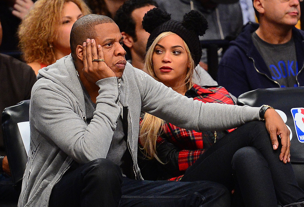 . (L-R) Singer Jay Z and his wife singer Beyonce watch the NBA game between the Philadelphia 76ers and the Brooklyn Nets at the Barclays Center in New York, February 3, 2014       (EMMANUEL DUNAND/AFP/Getty Images)