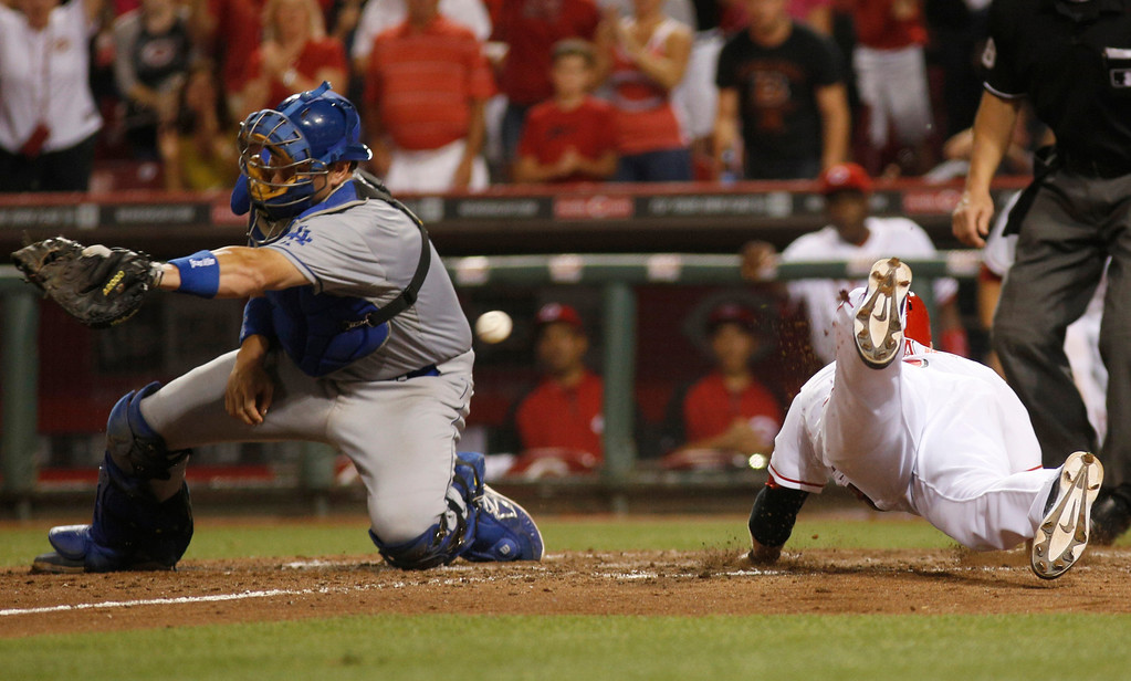 . Cincinnati Reds\' Zack Cozart, right, slides into home plate scoring the winning run past Los Angeles Dodgers catcher A.J. Ellis, left,  after a Ryan Hanigan double in the ninth inning during a baseball game, Sunday, Sept. 8, 2013, in Cincinnati. The Reds won 3-2. (AP Photo/David Kohl)