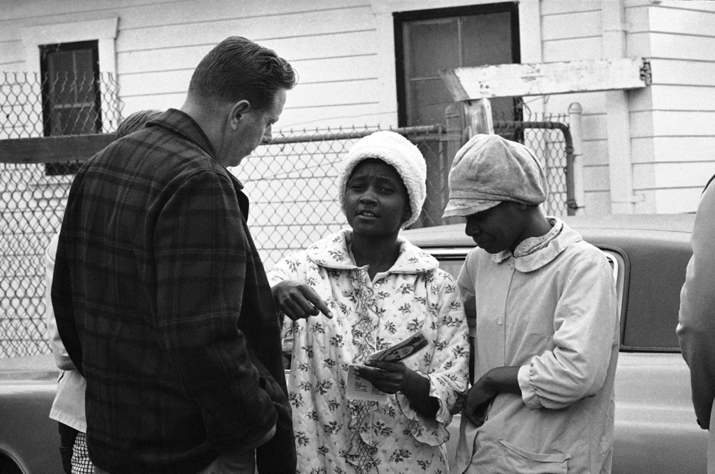 . An FBI agent shows photos of Symbionese Liberation army members to residents living near a south-central in Los Angeles house which police stormed Friday in the belief three SLA members were inside, May 17, 1974. The house was found to be empty. Denise Woods, center, is holding the photos, one of which is of kidnapped Patricia Hearst. (AP Photo)