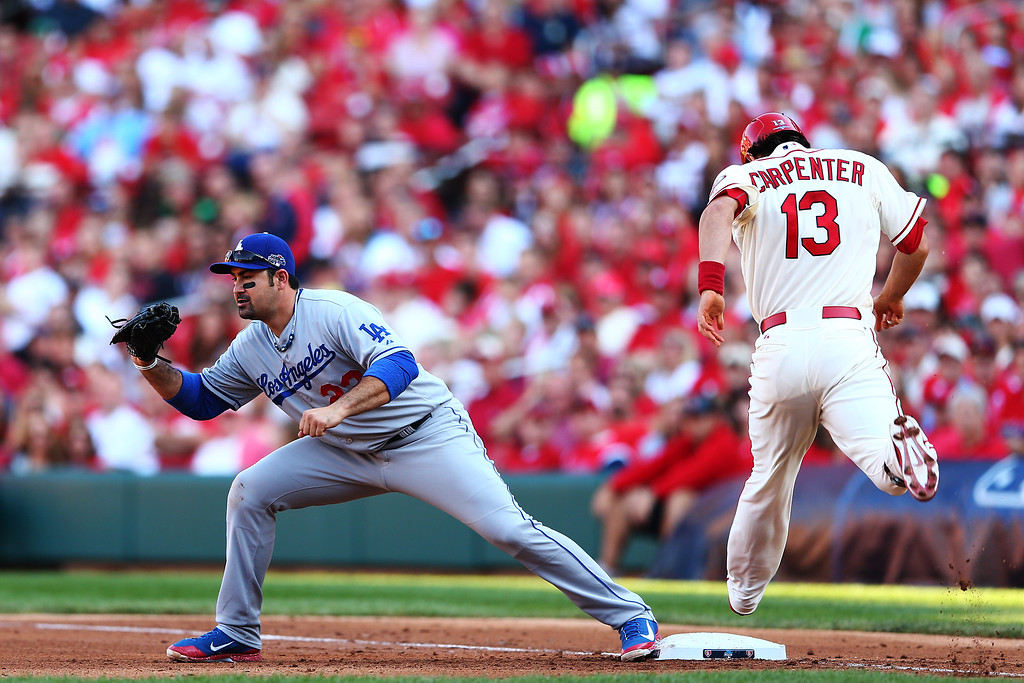. ST LOUIS, MO - OCTOBER 12:  Matt Carpenter #13 of the St. Louis Cardinals is out at first by Adrian Gonzalez #23 of the Los Angeles Dodgers in the third inning during Game Two of the National League Championship Series at Busch Stadium on October 12, 2013 in St Louis, Missouri.  (Photo by Elsa/Getty Images)