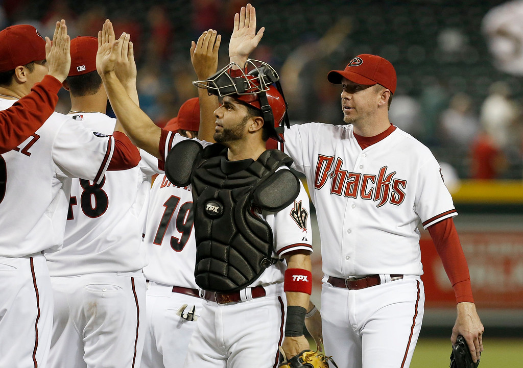 . Arizona Diamondbacks\' Wil Nieves, and Brad Ziegler, right, get high-fives from teammates after the final out in the ninth inning of a baseball game on Monday, Sept. 16, 2013, in Phoenix.  The Diamondbacks defeated the Dodgers 2-1. (AP Photo/Ross D. Franklin)