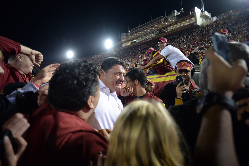 . USC coach Ed Orgeron makes his way off the field surrounded by fans after defeating Stanford during their game at the Los Angeles Memorial Coliseum Saturday, November 16, 2013. USC beat Stanford 20-17. (Photos by Hans Gutknecht/Los Angeles Daily News)