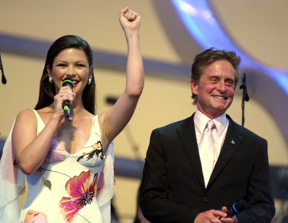 . U.S. actor Michael Douglas and his wife Catherine Zeta Jones on the stage during the Pavarotti & friends 2001 annual charity concert at the Parco novi Sad in Modena, Italy, Tuesday May 29, 2001. (AP Photo/Luca Bruno)
