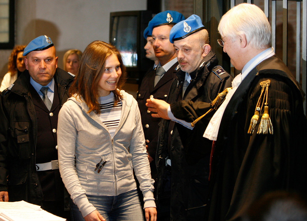 . Amanda Knox smiles to her lawyer Luciano Ghirga  as she arrives at Perugia\'s court, Italy, Friday, Jan. 16, 2009.  Knox, an American college student from Seattle and her Italian former boyfriend Raffaele Sollecito are accused of sexually assaulting and murdering her roommate, Meredith Kercher, in a slaying that shocked Italy.  (AP Photo/Alessandra Tarantino)