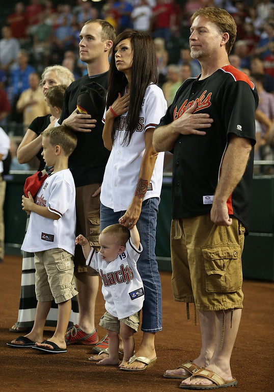 . PHOENIX, AZ - JULY 08:  Julianne Ashcraft, wife to fallen firefighter Andrew Ashcraft, (c) stands attended for the National Anthem with family members before the MLB game between the Arizona Diamondbacks and the Los Angeles Dodgers at Chase Field on July 8, 2013 in Phoenix, Arizona.  The Arizona Diamondbacks are honoring the 19 Granite Mountain Interagency Hotshot Crew firefighters who died battling a fast-moving wildfire near Yarnell, AZ. (Photo by Christian Petersen/Getty Images)