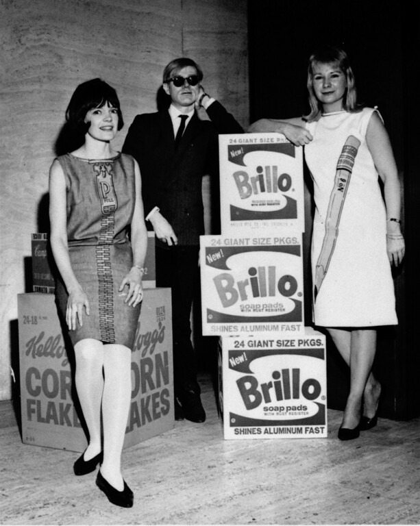 ". Andy Warhol shows his latest work ""Brillo\"",  at the Four Seasons\' showing of the nation\'s largest collection of pop art, March 14, 1965, for the benefit of the Mental Health campaign.  He is joined by model Robin MacDonald and artist Jane Wagner, (right) both wearing pop dresses designed by Crazy Horse.  (AP Photo/ho)"