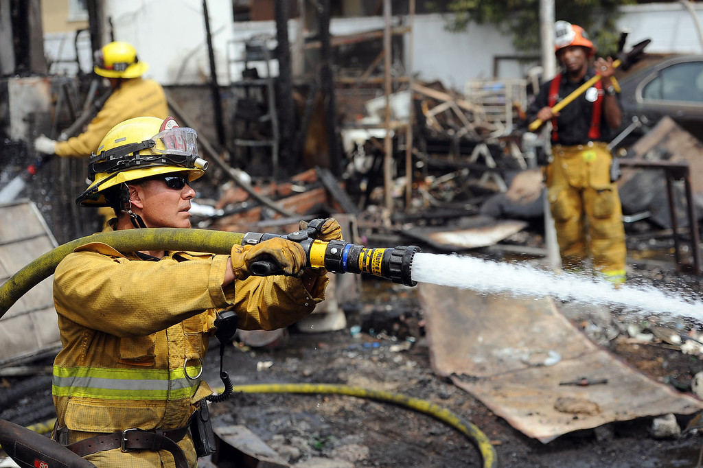 . Firefighters douse hotspots after a structure fire damaged two homes in the 17800 block of Vanowen St. in Reseda, CA April 10, 2014.(Andy Holzman/Los Angeles Daily News)
