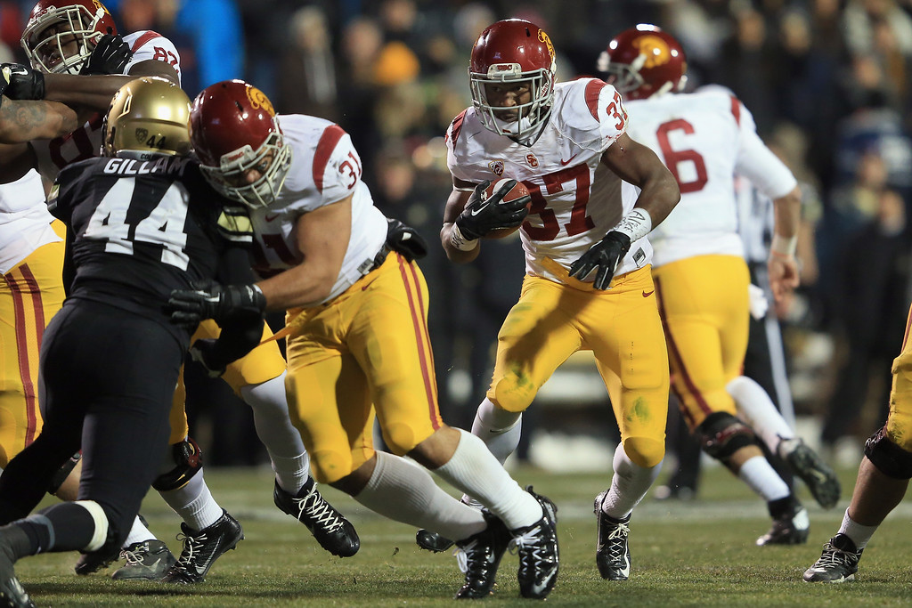 . USC 47, COLORADO 29<br /> Nov. 23, 2013; Folsom Field, Boulder, Colo. Tailback Javorius Allen delivered another three-touchdown game as he ran for 145 yards in 29-degree weather -- the second-coldest kickoff in Trojans history. Cody Kessler threw for 184 yards and two touchdowns for USC (9-3, 6-2), which racked up its fifth consecutive victory. USC jumped out to a 37-7 lead before Colorado (4-7, 1-7) closed to within 40-29 with 3:19 to play. However, USC recovered an onside kick and fullback Soma Vainuku rumbled 52 yards for the final score.    (Photo by Doug Pensinger/Getty Images)