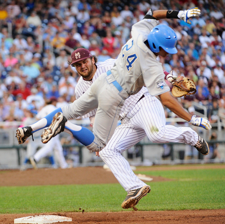 . Mississippi State first baseman Wes Rea, rear, and UCLA\'s Brian Carroll (24) are sent spinning after they collide at first base in the fourth inning of Game 1 of the NCAA College World Series best-of-three finals, Monday, June 24, 2013, in Omaha, Neb. Carroll was safe on the play. (AP Photo/Francis Gardler)