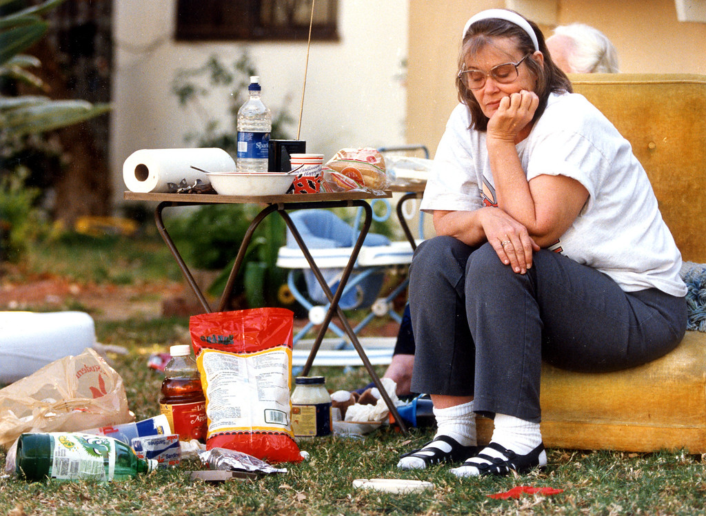 . A woman sits outside as she listens to reports about aftershocks.   1/17/94.   Los Angeles Daily News file photo