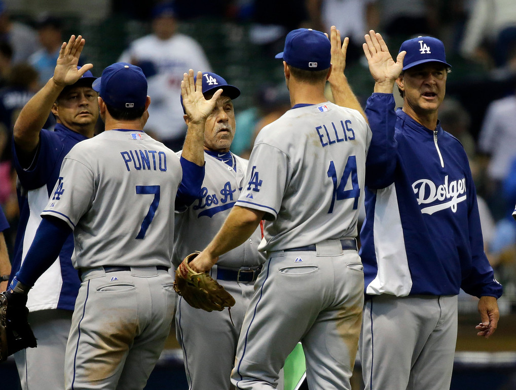 . Los Angeles Dodgers manager Don Mattingly, right, celebrates with his team after a baseball game against the Milwaukee Brewers Wednesday, May 22, 2013, in Milwaukee. The Dodgers won 9-2. (AP Photo/Morry Gash)