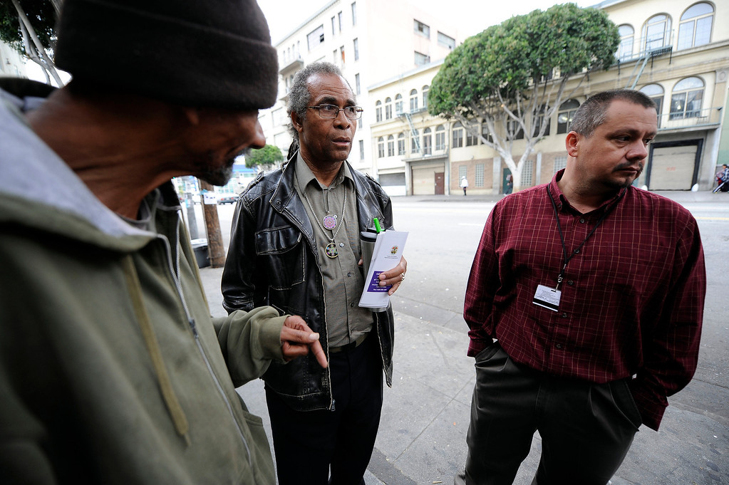 . JWCH Institute Lead Community Outreach Worker Christopher Mack and Enrollment and Eligibility Department Manager Juan Rivera talk to Phillip Evan, 57-years-old, about health care in the Skid-row area of Los Angeles Wednesday, April 24, 2013. (Hans Gutknecht/Staff Photographer)