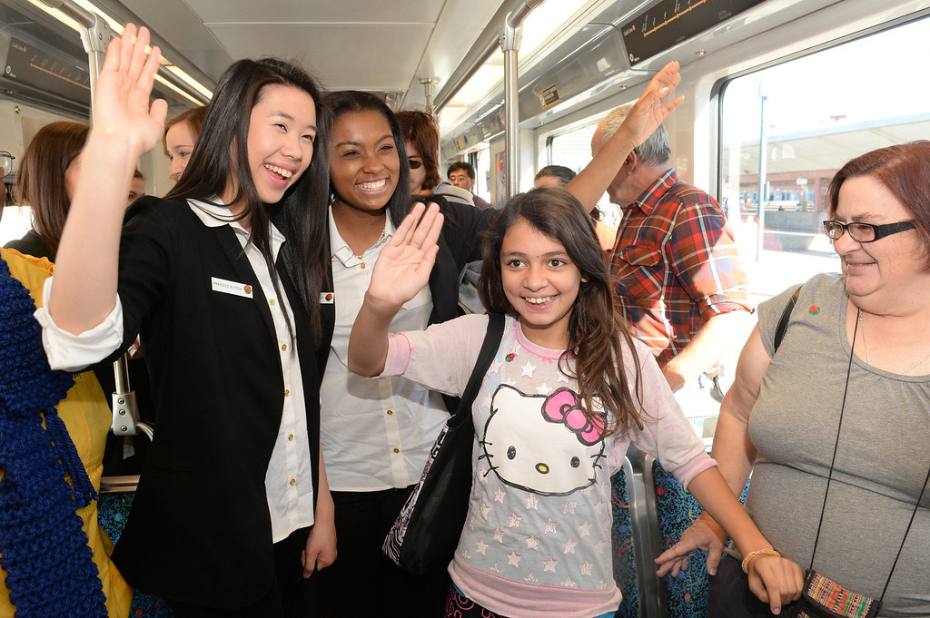 . The 2014 Tournament of Roses Princesses Elyssia Widjaja, left, and Kayla Johnson-Granberry, center, teach Karla White, 11, how to wave, with her grandmother, Debra White, as they ride the Metro gold Line from Union Station in Los Angeles on Friday December 27, 2013. The event is to commemorate the 10th official year of Metro Rail service to the Tournament of Roses parade events at Union Station. (Staff Photo by Keith Durflinger/Pasadena Star-News)
