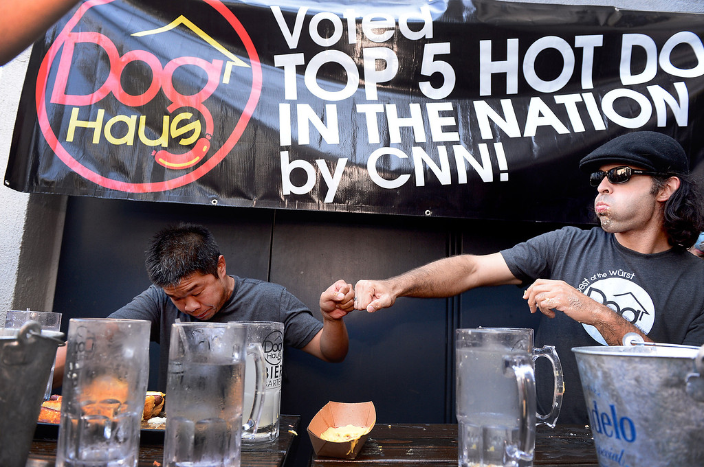 . Jimmy Lin, of Anaheim, left, gets fist pumped by third place winner Naader Reda, of Victorville as he wins the First Annual Hot Dog Eating Competition at Dog Haus Biergarten in Old Pasadena Saturday, July 6, 2013. Lin ate 11 dogs, 3 during a tiebreaker. (SGVN/Staff Photo by Sarah Reingewirtz)