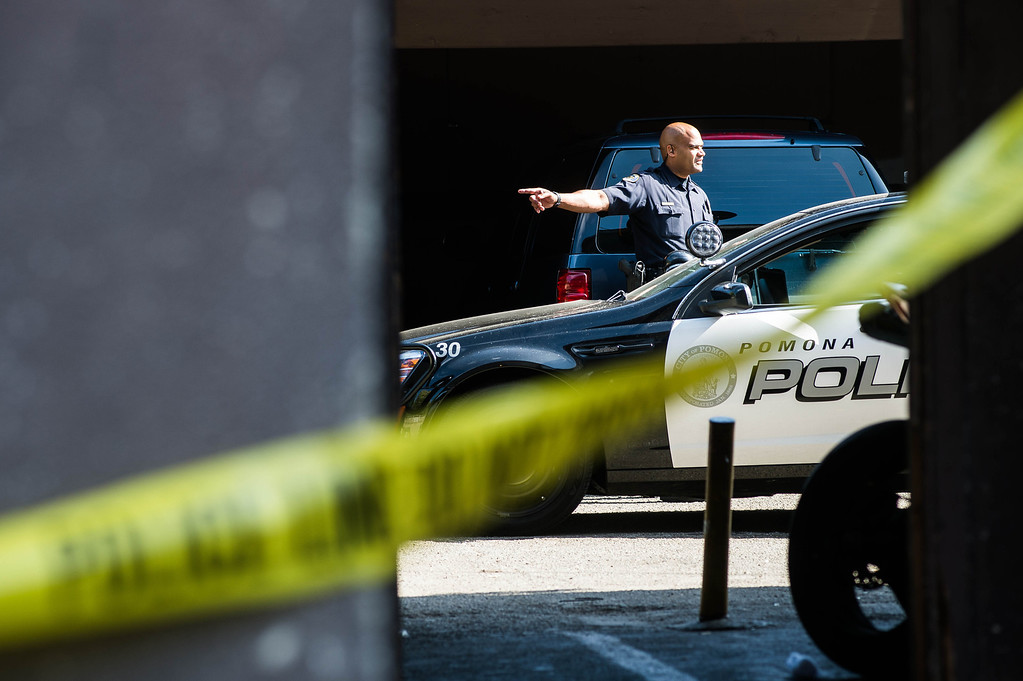 . Police investigate an early morning shooting death of a woman in an apartment complex in the 700 block of San Francisco Avenue in Pomona on Monday, June 14, 2014. The body was found in the carport area behind the complex. (Photo by Watchara Phomicinda/ San Gabriel Valley Tribune)