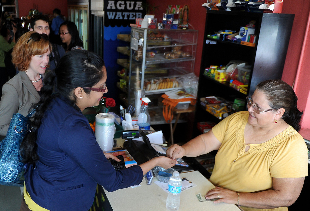 . Maria Avilia, right, makes sales during a press conference announcing new data on the availability and marketing of tobacco, alcohol and food products in stores at Euclid Market in Los Angeles on Wednesday, March 5, 2014.  (Keith Birmingham Pasadena Star-News)
