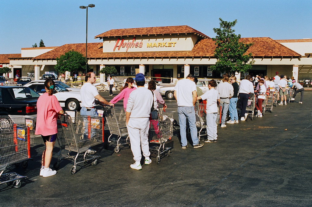 . Customers wait outside the Hughes Market in Valencia for a chance to buy water and food. At many stores, the wait in line lasted for hours.   David Crane/Los Angeles Daily News photo
