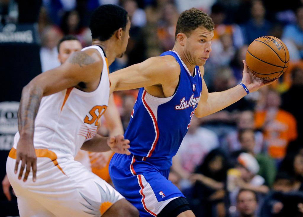 . Los Angeles Clippers forward Blake Griffin (32), right, pushes the ball upcourt as Phoenix Suns forward Channing Frye defends during the first half of an NBA basketball game on Wednesday, April 2, 2014, in Phoenix. (AP Photo/Matt York)
