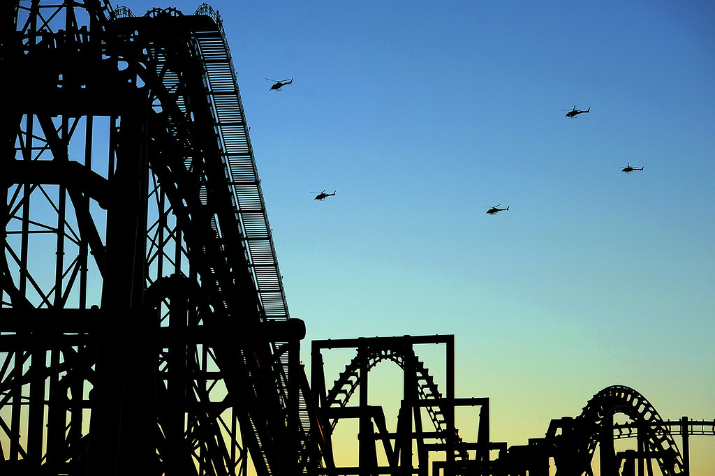 . News helicopters hover over Six Flags Magic Mountain as emergency personnel tend to injured and stranded riders on the Ninja ride July 7, 2014 in Valencia, CA.  Riders were injured after a tree limb fell on the track around 5:30 PM Monday.(Andy Holzman/Los Angeles Daily News)