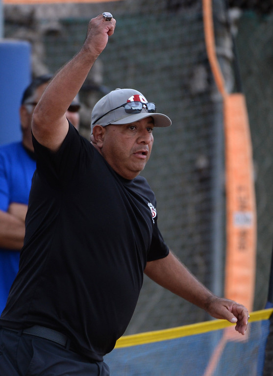 . La Serna\'s third base coach waves Taylor Becerra (not pictured) home on a RBI double by Danielle Garcielita (not pictured) in the fourth inning of a prep playoff softball game at Bishop Amat High School in La Puente, Calif., on Thursday, May 22, 2014. La Serna won 6-0.   (Keith Birmingham/Pasadena Star-News)