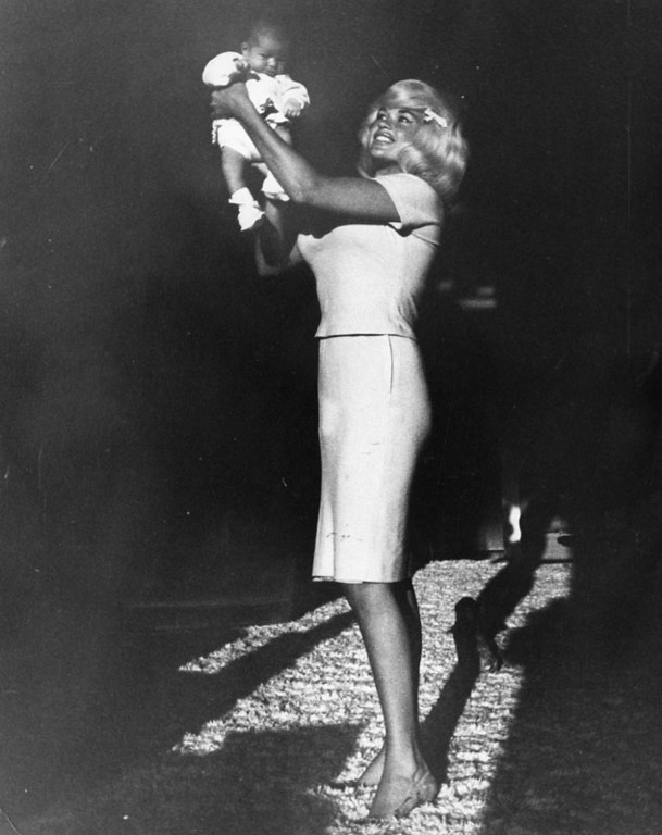 . Photograph dated March 7, 1964 shows Jayne Mansfield smiling and holding up her baby daughter Mariska Hargitay.   (Los Angeles Public Library)