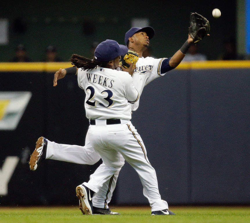 . Milwaukee Brewers\' Jean Segura and Rickie Weeks (23) can\'t come up with a ball hit by Los Angeles Dodgers\' Matt Kemp during the sixth inning of a baseball game Wednesday, May 22, 2013, in Milwaukee. (AP Photo/Morry Gash)