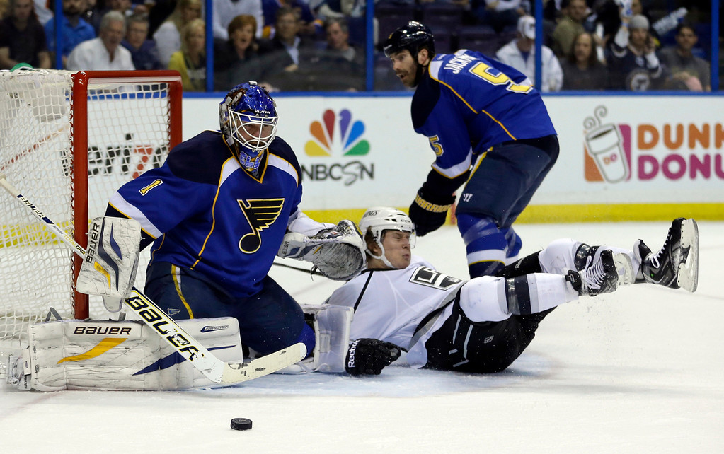 . St. Louis Blues goalie Brian Elliott, left, watches the puck as Los Angeles Kings\' Tyler Toffoli falls and Blues\' Barret Jackman skates past during the first period in Game 5 of a first-round NHL hockey Stanley Cup playoff series, Wednesday, May 8, 2013, in St. Louis. (AP Photo/Jeff Roberson)