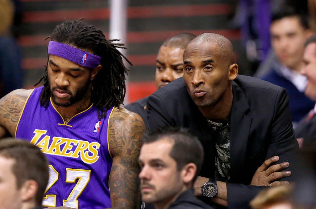 . Injjured Los Angeles Lakers player Kobe Bryant, right, sits on the end of the team bench next to Jordan Hill, left, during the first half of an NBA basketball game against the Phoenix Suns on Wednesday, Jan. 15, 2014, in Phoenix. (AP Photo/Ross D. Franklin)