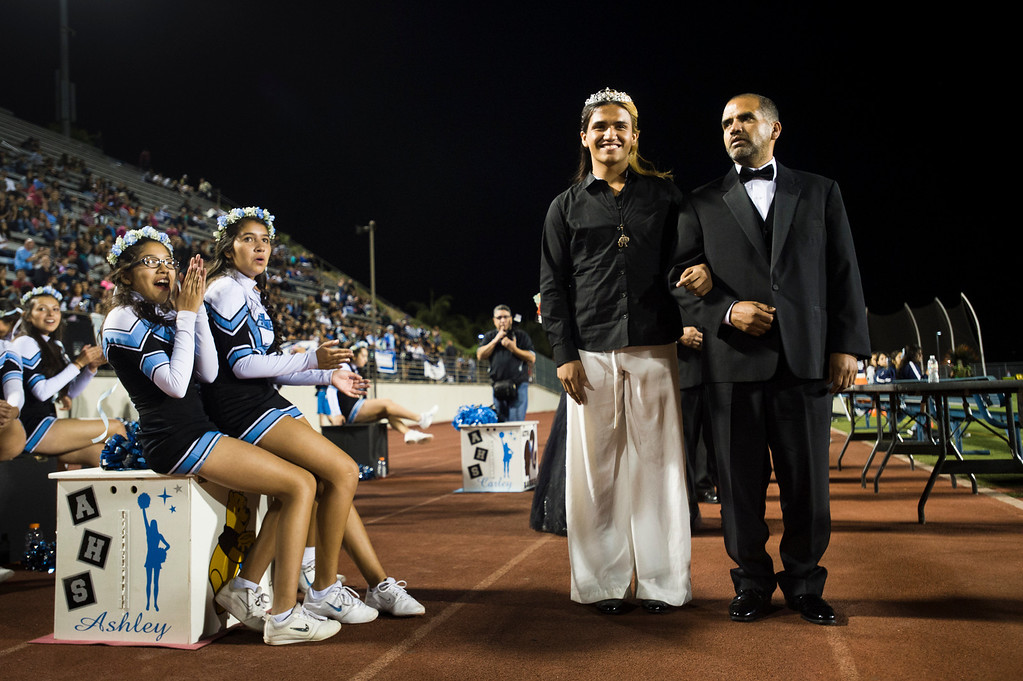 . Patrick Cordova, 16, a transgender senior walks with his dad, Jose Cordova, during Azusa High 2013 Homecoming halftime at Citrus College Stadium in Glendora on Friday night, Sept. 27, 2013.( Photo by Watchara Phomicinda/ San Gabriel Valley Tribune)