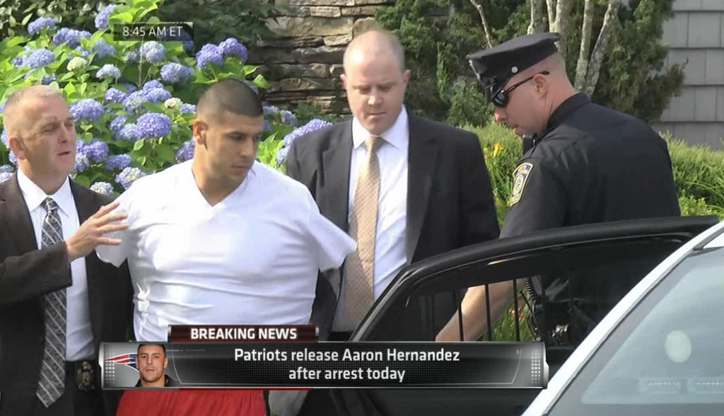 . In this image taken from video, police escort Aaron Hernandez from his home in handcuffs in Attleboro, Mass., Wednesday, June 26, 2013. Hernandez was taken from his home more than a week after a Boston semi-pro football player was found dead in an industrial park a mile from Hernandez\'s house. (AP Photo/ESPN)