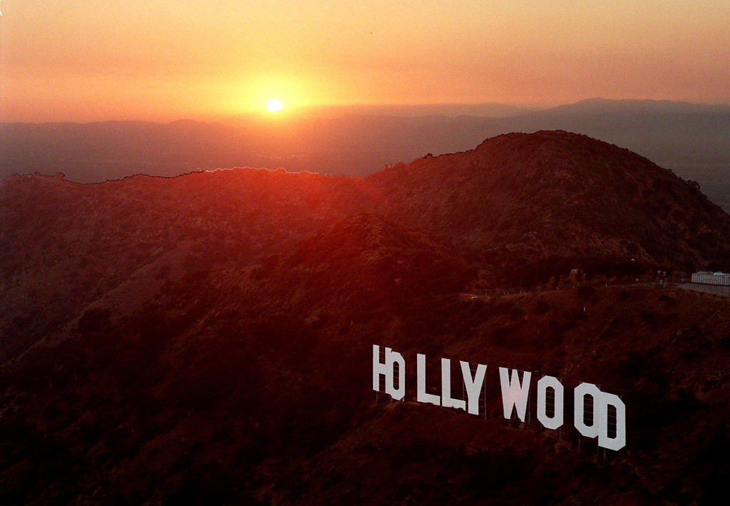 . Setting behind mountains and a thick layer of haze, the sun casts a warm glow on the Hollywood sign overlooking Los Angeles late Wednesday, June 30, 1999. For a century and a half California has been a destination for every conceivable sort of adventurer. (AP Photo/Reed Saxon)