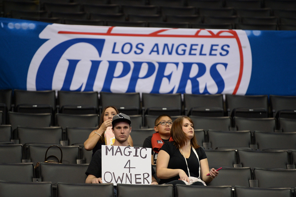 ". Fans holds a sign reading ""Magic 4 Owner\"" before the start of the NBA playoff game between the Los Angeles Clippers and the Golden State Warriors, April 29, 2014 at Staples Center in Los Angeles, California.  The NBA banned Clippers owner Donald Sterling from professional basketball for life over racist comments that the league\'s commissioner dubbed \""deeply offensive and harmful.\""   Fans and observers are speculating as to whether retired NBA superstar Magic Johnson would become new owner of the Clippers.               (ROBYN BECK/AFP/Getty Images)"